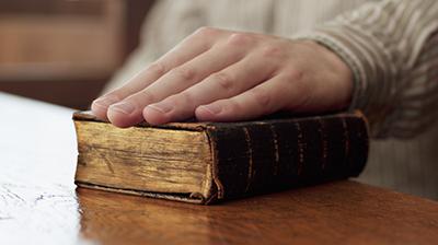 Hand of witness on Bible in courtroom --- Image by © 237/Chris Ryan/Ocean/Corbis